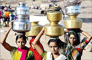Residents of a colony in New Delhi leave after filling their containers from a water tanker.