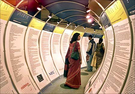 Indians look at IT posters during the seventh edition of the IT industry exposition.