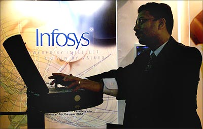 A visitor works on a laptop at a stall advertising Infosys.