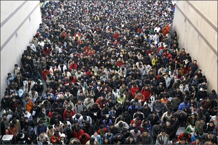 Applicants walk into the entrance of a university to take part in the entrance exam for postgraduate studies in Wuhan.