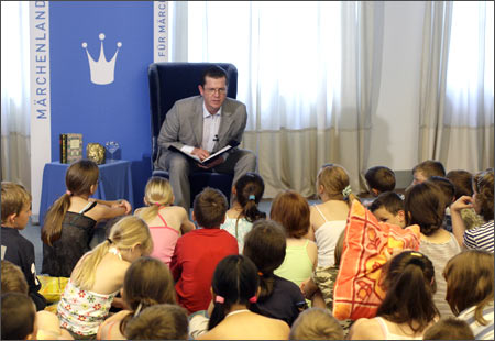 German Economy and Technology Minister Karl-Theodor zu Guttenberg reads a fairy tale to children.