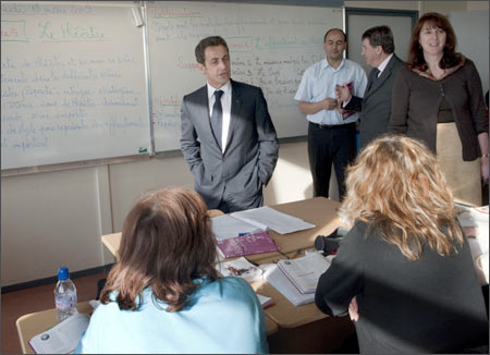 French President Nicolas Sarkozy (C), education minister Xavier Darcos (2nd R) speak with students.