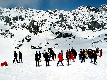 Indian tourists walk on snow.