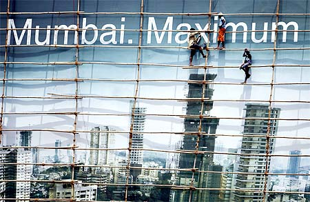 Labourers work on a billboard in Mumbai. Job-losses in India are likely to intensify, says a study.