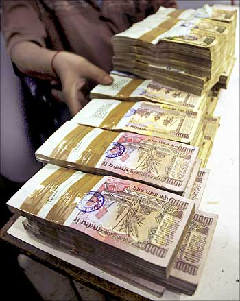A bank employee counts bundles of Indian currency.
