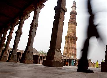 A tourist walks past the illuminated 72.55 (238 ft) meter high Qutab Minar in New Delhi.