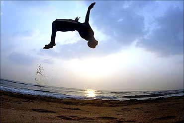 A boy somersaults at Marina beach as part of his routine morning exercise in Chennai.