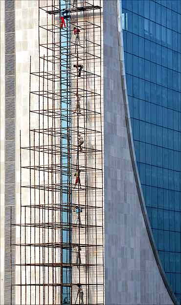 Men work at the construction site of a high-rise commercial building in New Delhi.