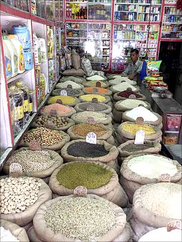 A retail trader arranges a bag containing pulses inside his shop in Jammu.