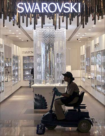An employee operates a floor cleaning machine in front of a Swarovski showroom in Mumbai.