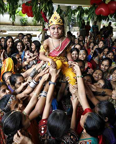 A boy dressed as Lord Krishna is carried during Janmashtami celebrations.