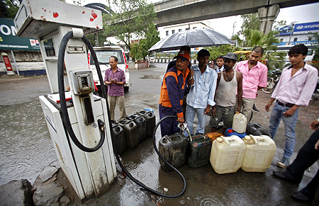 A worker fills diesel in containers at a fuel station during a rain shower at Noida.