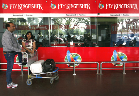 Passengers stand at a Kingfisher Airlines reservation office at the domestic airport in Kolkata.
