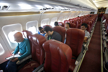 Kingfisher Airlines passengers sit on a plane after takeoff from Mumbai's domestic airport.