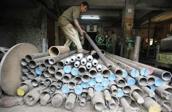 A worker checks an iron pipe that will be used to make spare parts for a drilling machine inside a factory in Kolkata.