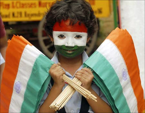 A school girl with her face painted in the colours of the Indian national flag holds flags during Independence Day celebrations at a school in Patna