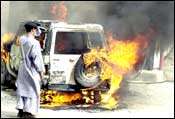 A man looks at a car set on fire by an angry mob