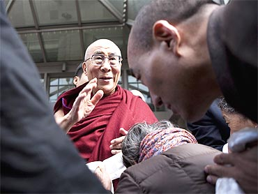 The Dalai Lama greets supporters outside of his hotel