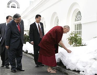 The Dalai Lama touches the snow as he walks outside the White House