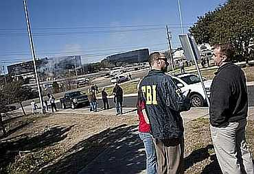 FBI personnel talk to people near the site