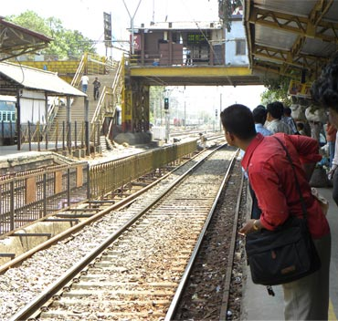 Commuters wait for a train at Dadar station in Mumbai