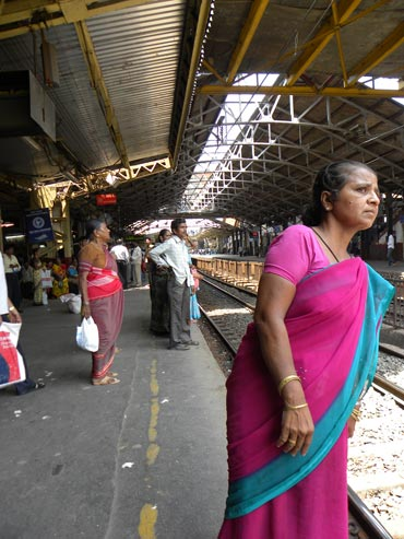 A woman cranes her neck, hoping to see a train in Mumbai