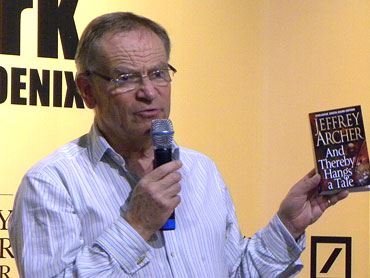 Jeffrey Archer holds up a copy of his new book, And Thereby Hangs a Tale