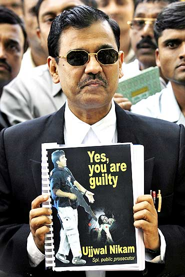 Special Prosecutor Ujjwal Nikam shows a copy of the verdict to the media outside the Arthur Road Jail in Mumbai, where the trial of Mohammad Ajmal Kasab, the suspected lone surviving gunman of the 2008 Mumbai attacks, is being held.