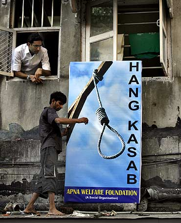 A resident places a billboard of Kasab outside a residential building near the Leopold Cafe, one of the sites of last year's terrorist attacks