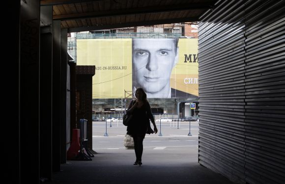 A pedestrian walks past a poster with the face of Russian billionaire Mikhail Prokhorov hanging near Moscow's Red Square