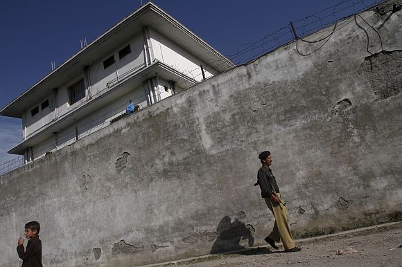 Pakistani security personnel walk past the compound in Abbottabad where Osama bin Laden was killed by US Special Forces