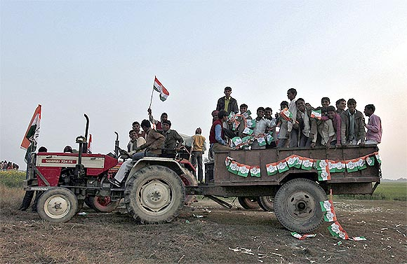 People travel on a tractor after attending an election campaign rally