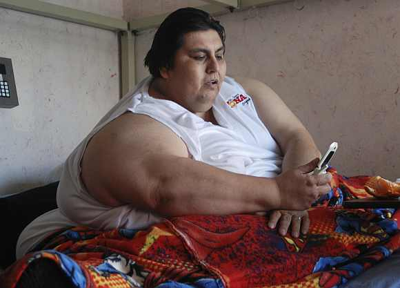 Manuel Uribe writes a text message on his cell phone at his mother's home in the suburb of San Nicolas de los Garza, Monterrey