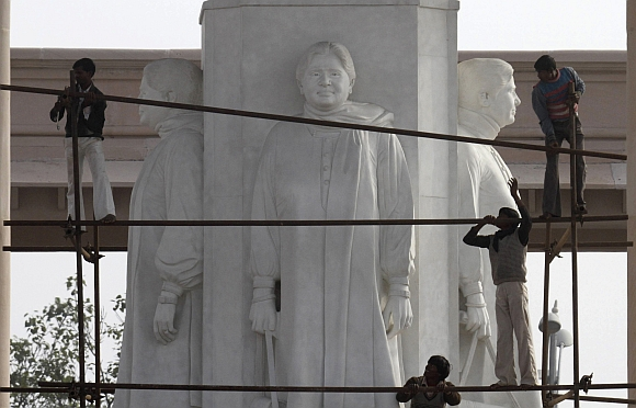Workers erect a scaffolding to cover statues of Uttar Pradesh Chief Minister Mayawati in Lucknow