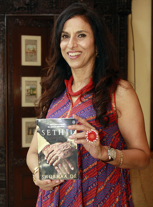 Shobhaa De holds up a copy of her latest book, Sethji