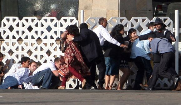 People duck for cover as gunshots are fired from inside Hotel Taj Mahal during the 26/11 terror attacks in Mumbai