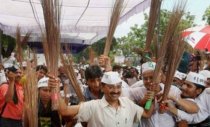 Kejriwal with the symbol of AAP along with his party men in New Delhi