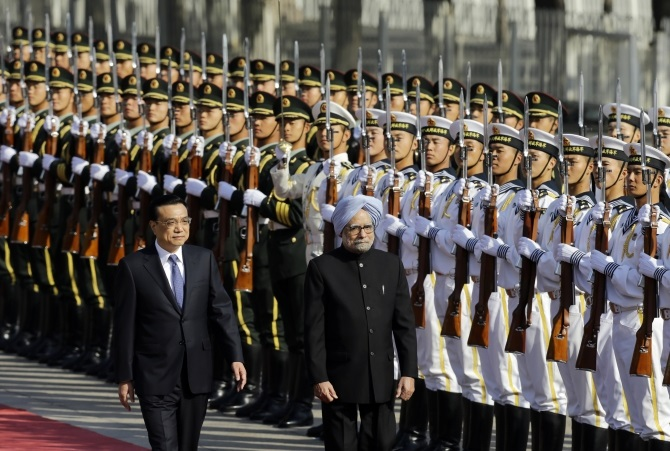 Prime Minister Manmohan Singh inspects a guard of honour with China's Premier Li Keqiang during a welcome ceremony outside the Great Hall of the People in Beijing