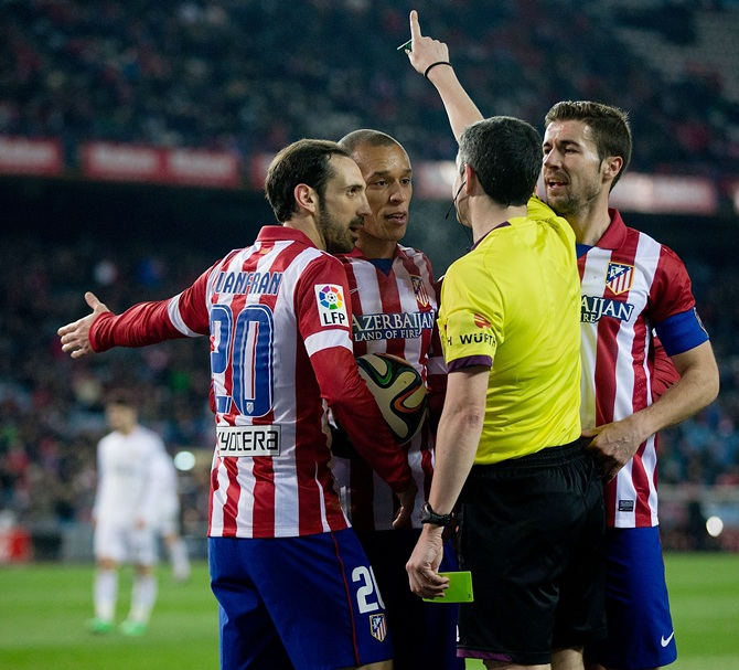 Joao Miranda, second left of Atletico de Madrid and his teammates Juan Francisco Torres alias Juanfran, left, and Gabi Fernandez argue with referee Undiano Mallenco.