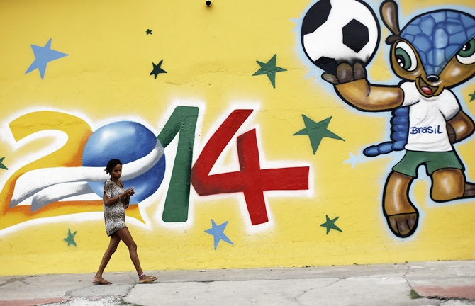 A woman walks past a graffiti painted with the   official mascot of the 2014 World Cup, Fuleco the Armadillo, in Sao Paulo