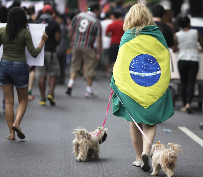A woman walks her dogs during a protest on the streets near the Maracana stadium in Rio de Janeiro