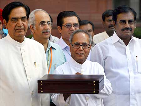 Finance minister Pranab Mukherjee smiles as he leaves his office to present the Budget.