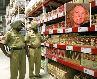 Policemen stand inside the first cash-and-carry Wal-Mart store in Amritsar, Punjab. (Inset: Christy Walton, the world's richest woman)