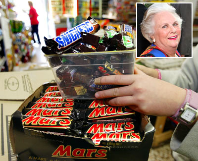 A shopkeeper removes Mars Bars and Snickers Bars from the shelves of her convenience store (Inset: Jacqueline Mars)
