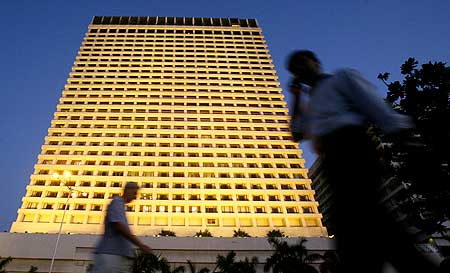 People walk past the lit-up Trident Hotel, Mumbai