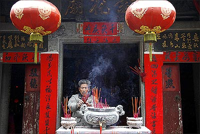 A resident burns incense as he prays in a small temple in the village of Wukan in Lufeng county, Guangdong province.