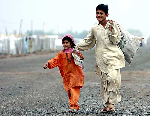 Evacuees from Buner walk near a camp on the outskirts of Peshawar