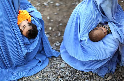 Displaced women hold their infants at a repatriation centre in Peshawar