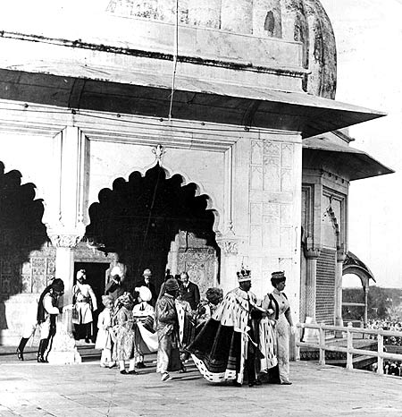 :  King George V and Queen Mary walk hand in hand as they leave a Delhi fort after greeting the crowds below during their royal tour of India