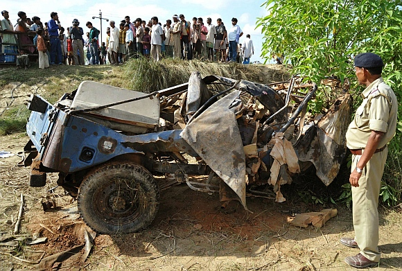A policeman stands besides the wreckage of a security patrol vehicle that was damaged in a landmine blast in Bihar